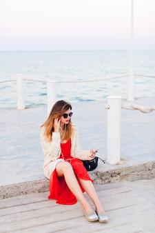 Piękna dziewczyna w czerwonej sukience i białej kurtce siedzi na molo, uśmiecha się i słucha muzyki na słuchawkach w smartfonie.