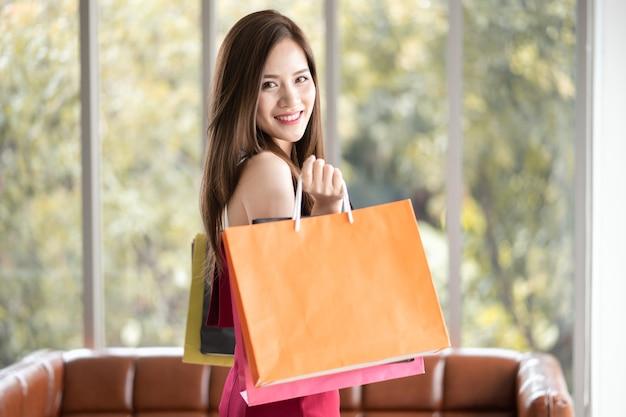 Piękna dziewczyna w czerwonej sukience lubi robić zakupy. ma wiele torebek i kupuje je od su