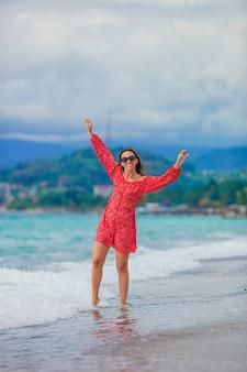 Piękna dziewczyna w czerwonej sukience na plaży zabawy