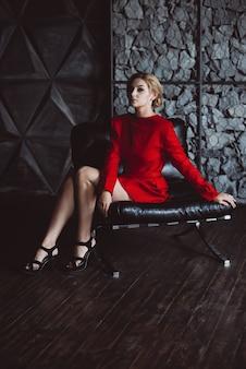 Piękna dziewczyna w czerwonej sukience niestety siedzi na skórzanym krześle w stylu loftu. piękno, moda.