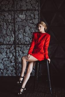 Piękna dziewczyna w czerwonej sukience siedzi niestety na stołku barowym w stylu loftu. piękno, moda.