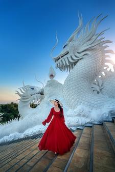 Piękna dziewczyna w czerwonej sukience spaceru w bramie świątyni