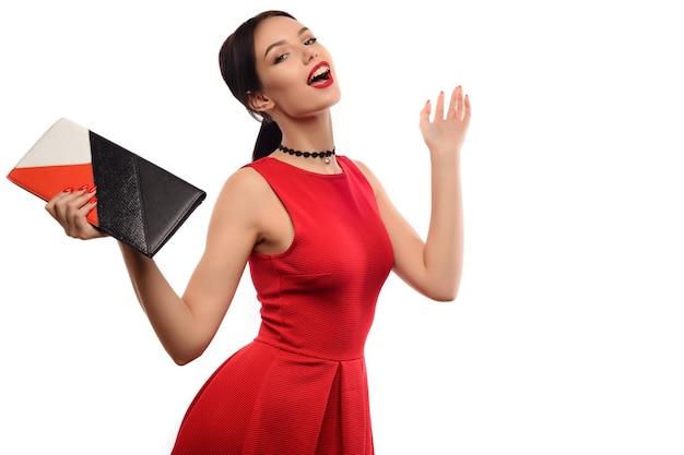 Piękna dziewczyna w czerwonej sukience z kolorową kopertówką cieszy się sprzedażą