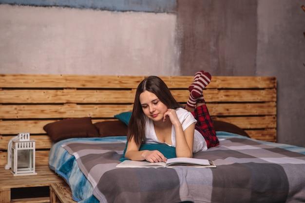 Piękna dziewczyna w czerwonych spodniach i skarpetkach leży na łóżku i czyta książkę, magazyn. hobby, czas wolny, wypoczynek. spojrzenie jest skierowane w dół na książkę.