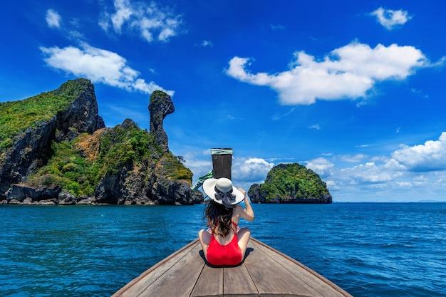 Piękna dziewczyna w czerwonym bikini na łodzi na wyspie koh kai, tajlandia.