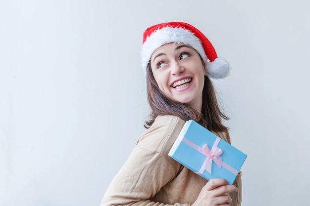 Piękna dziewczyna w czerwonym kapeluszu santa claus w ręku trzyma niebieskie pudełko na białym tle. portret młodej kobiety, prawdziwe emocje. koncepcja święta wesołych świąt i nowego roku.