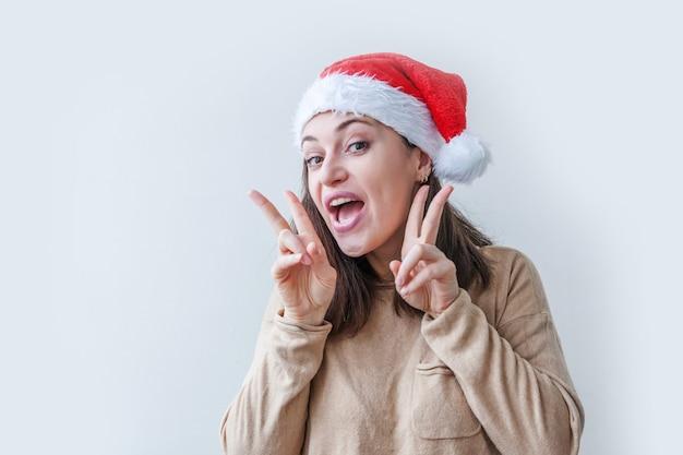 Piękna dziewczyna w czerwonym kapeluszu świętego mikołaja na białym tle. zimowy portret młodej kobiety. koncepcja święta wesołych świąt i nowego roku.