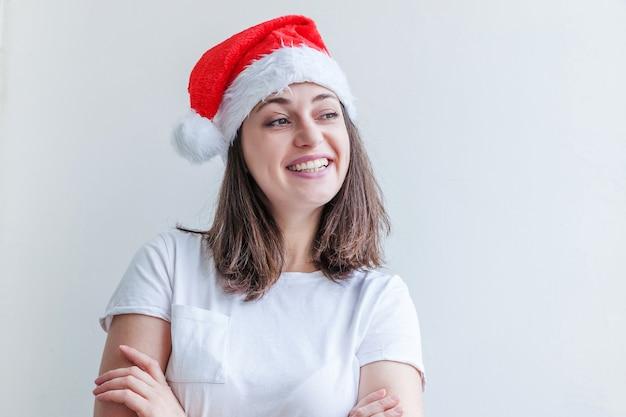 Piękna dziewczyna w czerwonym kapeluszu świętego mikołaja na białym tle