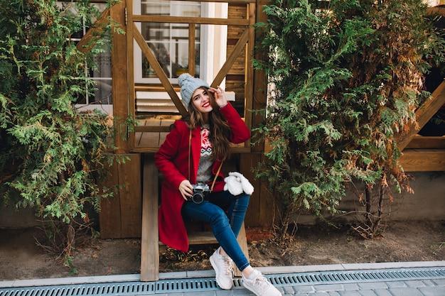Piękna dziewczyna w czerwonym płaszczu i czapce siedzi na drewnianych schodach. trzyma aparat na kolanach i uśmiecha się.