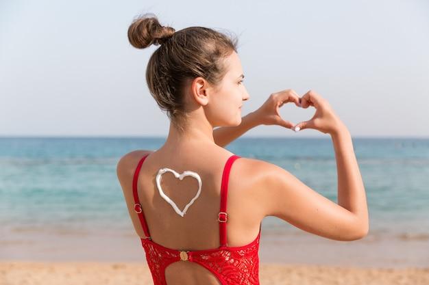 Piękna dziewczyna w czerwonym stroju kąpielowym z filtrem przeciwsłonecznym w kształcie serca z tyłu na plaży.