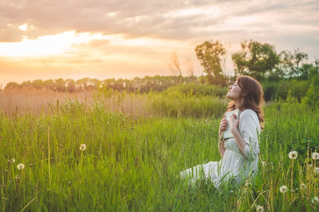 Piękna dziewczyna w dziedzinie, czytając książkę. dziewczyna siedzi na trawie, czytając książkę. odpoczynek i czytanie