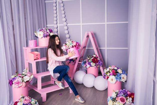 Piękna dziewczyna w dżinsach i różowym swetrze w studio z wystrojem kwiatów w koszach.