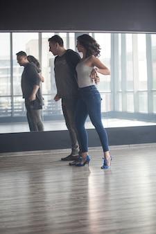 Piękna dziewczyna w dżinsach tańczy kizombę. wolność wyrażona podczas tańca. atrakcyjny taniec młodej kobiety.