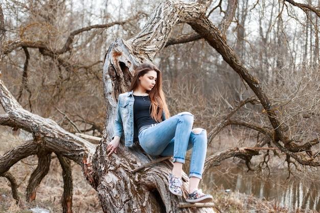 Piękna dziewczyna w dżinsowych spodenkach i dżinsowych spodenkach siedzi na drzewie