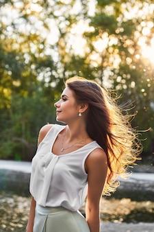 Piękna dziewczyna w eleganckiej sukni w parku