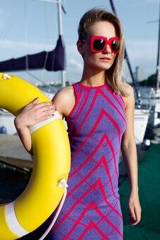 Piękna dziewczyna w fioletowej sukience i czerwonych okularach przeciwsłonecznych na przystani w pobliżu morza. dziewczyna trzyma żółtą kamizelkę ratunkową. portret moda