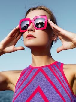 Piękna dziewczyna w fioletowej sukience i czerwonych okularach przeciwsłonecznych na przystani w pobliżu morza. portret mody