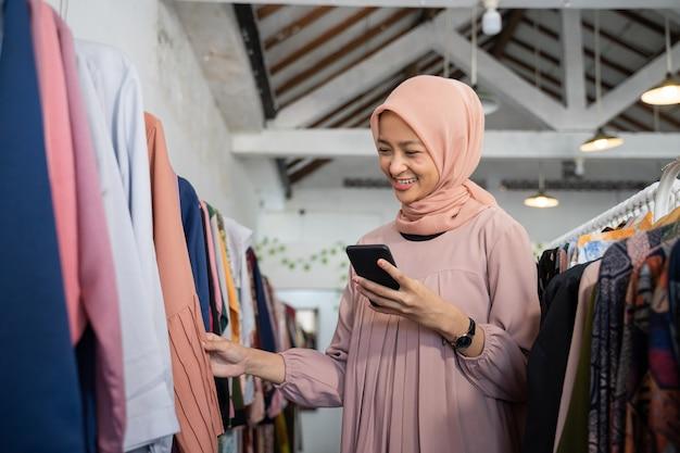 Piękna dziewczyna w hidżabie wybierająca ubrania trzymając smartfon