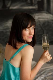 Piękna dziewczyna w jedwabnej piżamie przy lampce szampana
