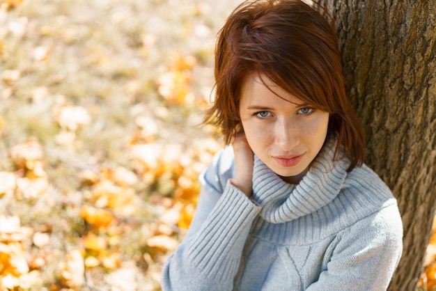 Piękna dziewczyna w jesiennym lesie kobieta siedzi przy drzewie w jesiennym parku w słoneczny dzień w k...