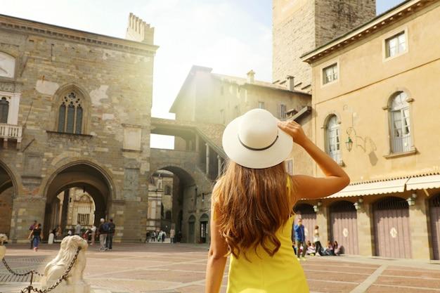 Piękna dziewczyna w kapeluszu odwiedzenie placu piazza vecchia w średniowiecznym starym mieście bergamo citta alta w regionie lombardia we włoszech.