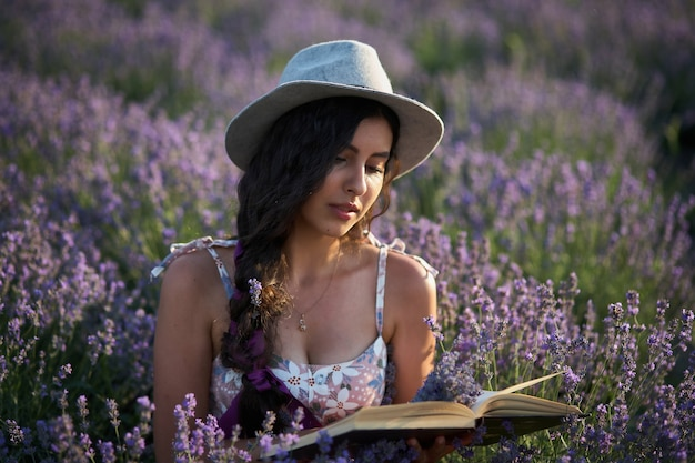 Piękna dziewczyna w kapeluszu siedzi w fioletowym polu lawendy i czytać książkę.