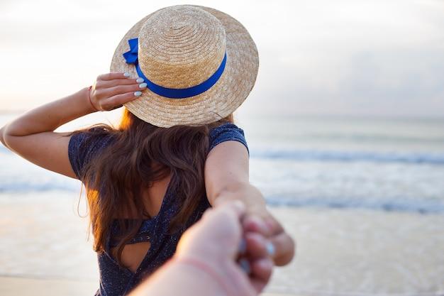 Piękna dziewczyna w kapeluszu trzyma rękę faceta
