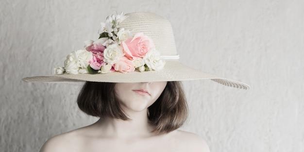 Piękna dziewczyna w kapeluszu z kwiatami na szarym tle