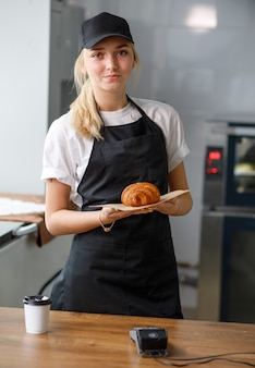 Piękna dziewczyna w kawiarni i piekarni trzyma rogalika