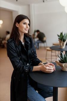 Piękna dziewczyna w kawiarni przy filiżance kawy