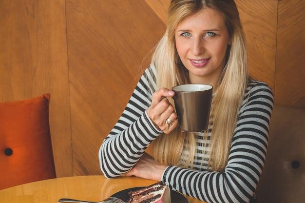 Piękna dziewczyna w kawiarni przy gorącej herbacie. hipster dziewczyna trzyma gorącą herbatę. napój orzeźwiający w słoneczny dzień.