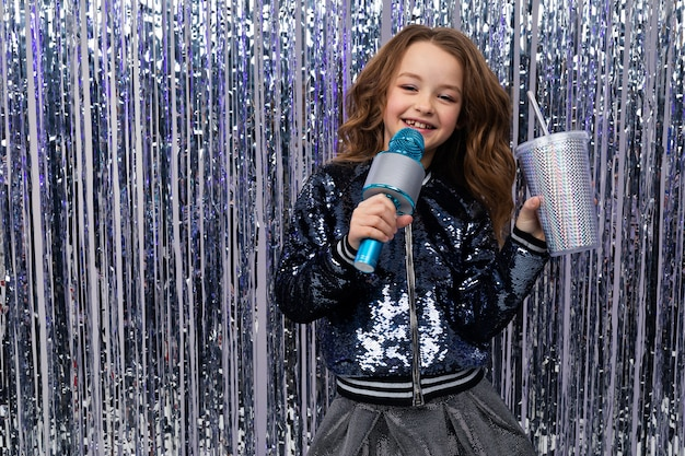 Piękna dziewczyna w konkursie talentów z mikrofonem i szklanką napoju na błyszczącej ścianie