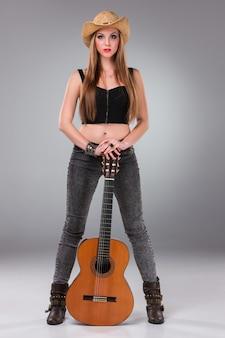 Piękna dziewczyna w kowbojskim kapeluszu i gitarze akustycznej.