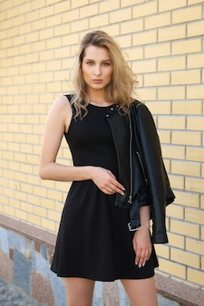 Piękna dziewczyna w krótkiej czarnej sukni i skórzanej kurtce na ulicie