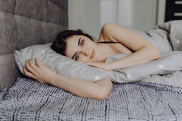 Piękna dziewczyna w łóżku. piękne młode kobiety kłama na kanapie i ono uśmiecha się przy kamerą