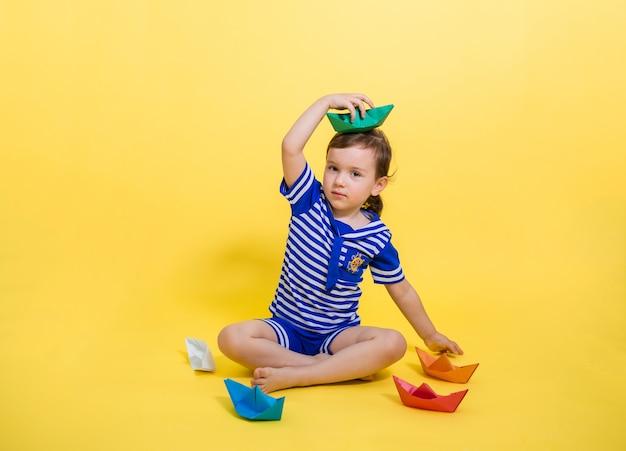 Piękna dziewczyna w marynarskim garniturze iz papierową łodzią na głowie na żółtej przestrzeni. mała dziewczynka otoczona kolorowymi papierowymi łodziami. dzień marynarki wojennej.