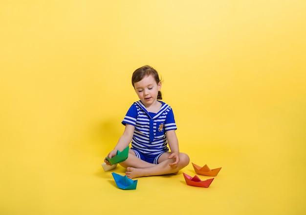Piękna dziewczyna w marynarskim garniturze patrzy na papierową łódkę na żółtej przestrzeni. dzień marynarki wojennej.