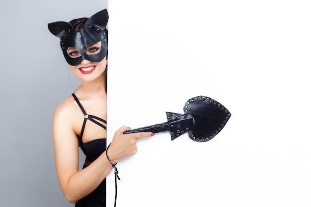 Piękna dziewczyna w masce kota. wskazuje wolne miejsce na tekst.