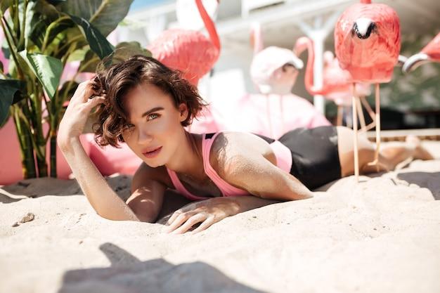Piękna dziewczyna w modnym stroju kąpielowym, leżąc na piasku i patrząc w kamerę ze sztucznymi różowymi flamingami w pobliżu na plaży