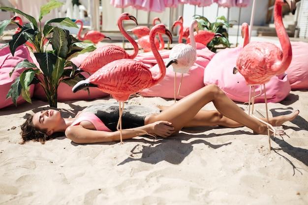 Piękna dziewczyna w modnym stroju kąpielowym leżąca na piasku ze sztucznymi różowymi flamingami i dużymi poduszkami w pobliżu na plaży.