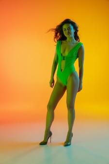 Piękna dziewczyna w modnym stroju kąpielowym na białym tle na gradientowym tle studio w świetle neonowym.