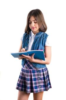 Piękna dziewczyna w mundurku szkolnym z notesem w ręku na białym