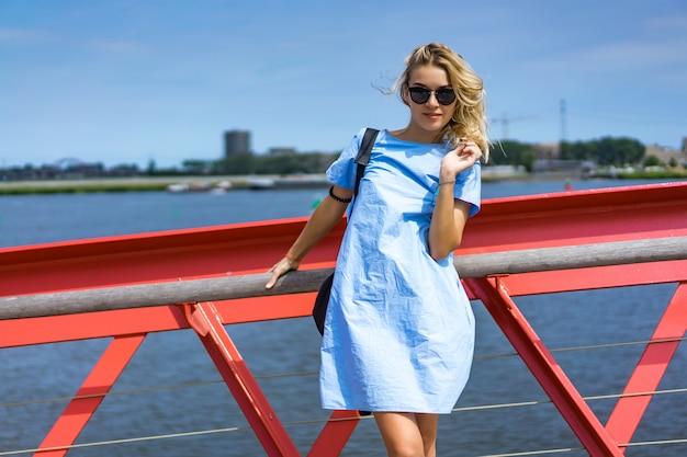 Piękna dziewczyna w niebieskiej sukience pozowanie na moście