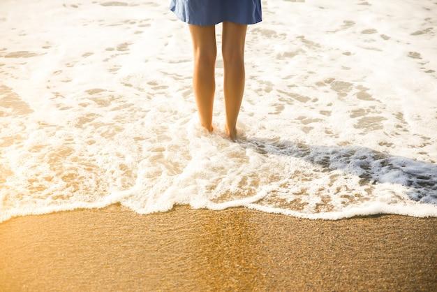 Piękna dziewczyna w niebieskiej sukience spaceruje po plaży. niesamowite letnie zdjęcie. kobieta w pobliżu morza. koncepcja podróży wakacje. smukłe nogi. ciepła woda oceaniczna.