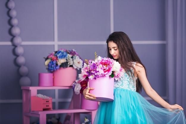 Piękna dziewczyna w niebieskiej sukience w studio z wystrojem kwiatów w koszach. skopiuj miejsce.