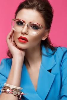 Piękna dziewczyna w niebieskim kolorze na różowym tle z kreatywnych makijaż i modny styl.