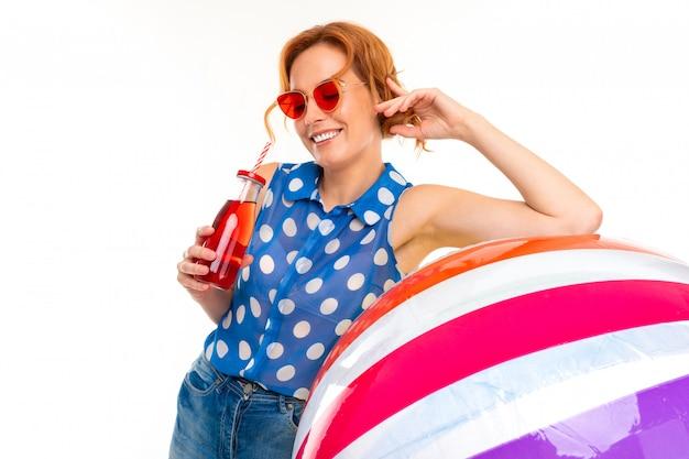 Piękna dziewczyna w okularach przeciwsłonecznych trzyma nadmuchiwaną dużą piłkę do pływania i pije koktajl na białej ścianie