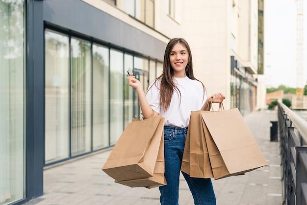 Piękna dziewczyna w okularach przeciwsłonecznych trzyma torby na zakupy i uśmiecha się idąc ulicą