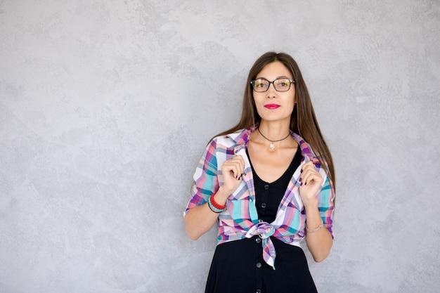 Piękna dziewczyna w okularach trzyma zgięte ramiona na kołnierzu