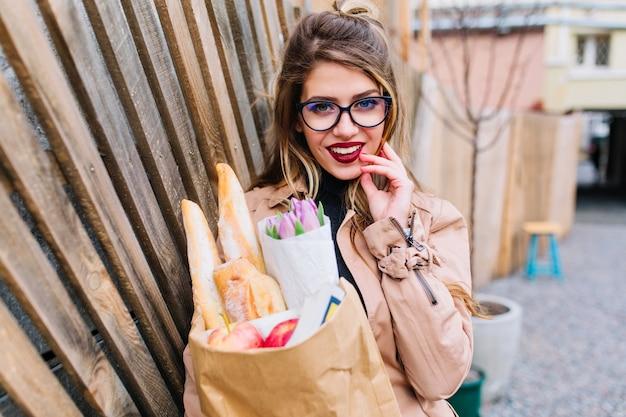 Piękna dziewczyna w okularach zalotnie dotyka twarzy stojącej na środku ulicy i uśmiechniętej. ładna młoda kobieta pozuje trzymając torbę ze sklepu i patrząc z zainteresowaniem.